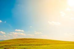 breites grünes Feld auf Rolling Hills und blauer Himmel mit Wolken unter Lizenzfreie Stockfotos