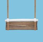 Breites hölzernes Schild mit dem Schnee, der an den Doppelseilen hängt Lizenzfreie Stockfotos