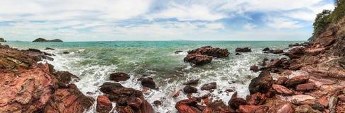Breites Panorama der hohen Auflösung von den Meereswellen, die auf roten Felsen zerquetschen lizenzfreie stockfotografie