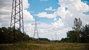 Breites Schuss timelapse von StromStromleitungen und von Hochspannungsmasten auf einem Feld in der Landschaft am Sommer Stockfoto