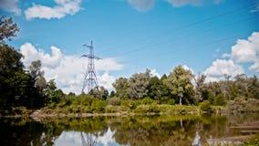 Breites Schuss timelapse von StromStromleitungen und von Hochspannungsmasten auf einem Feld in der Landschaft am Sommer nahe Stockbild