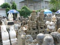 Breites Statuenfoto von den Männern, die auf chinesischen Wächterlöwen - Panjiayuan-Markt sitzen Stockfotografie