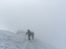 Breithorn summit. Two alpinists long the final ridge of breithorn occidentale, in a cloudy atmosphere. the summit will be reached in few minutes Stock Photos
