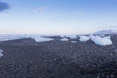 Brekend Ijs van gletsjer op het kleine zwarte strand van het rotszand, IJsland Stock Afbeeldingen