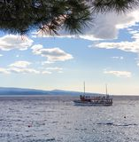 Brela, Croatia - June 24, 2019: A pleasure boat sails into the sea for a tour of the islands on a sunny summer day royalty free stock photography