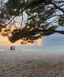 Brela Kroatië - Juni 5, 2019: Een reizend paar, een man en een vrouw zitten op een zonlanterfanter door het overzees in de avond stock foto
