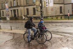 Brema, Germania, il 19 novembre 2017 Famiglia sulle biciclette con un piccolo bambino sulle vie nella pioggia fotografia stock libera da diritti