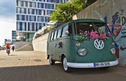 Brema, Germania - 17 luglio 2018 - furgone verde del T3 di VW con il grande logo di VW di bianco con la facciata di vetro moderna fotografie stock libere da diritti