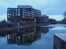 Bremen, Deutschland - Bürogebäude des Windkraftanlageherstellers Enercon an der Dämmerung, die im Wasser sich reflektiert lizenzfreies stockbild