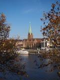 Bremen, Deutschland - Fluss Weser mit Kirche St. Martini gestaltet durch Bäume im Vordergrund mit schräg gelegenem Horizont stockfoto