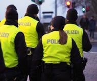 Bremen, Duitsland - de Groep politiemannen in zwarte uniformen en hallo-namelijk bekleedt het patrouilleren van de Kerstmismarkt stock afbeelding