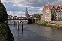 Bremen, Duitsland - de Rode gebouwen van de baksteenwaterkant en reusachtige brug over de rivier Weser met kerkspits in de afstan Stock Afbeeldingen