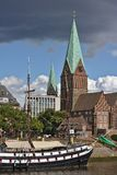 Bremen, Duitsland - Juli tiende, 2018 - Varend schip bij haar meertrossen met St Martini kerk in het achtergrondportret Stock Fotografie