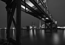 Bremen, Germany - Brightly lit harbor at night with rusty steel jetty above, lights reflecting in the water and various industrial. Plants in the distance stock images