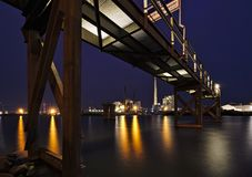 Bremen, Germany - Brightly lit harbor at night with rusty steel jetty above, yellow lights reflecting in the water and various ind. Ustrial plants in the royalty free stock images