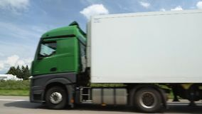 Slow motion German truck on German autobahn. Bremen, Germany - Circa 2017: Green cabin Mercedes-Benz truck with white trailer driving on the German Autobahn stock video footage