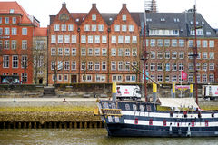 BREMEN, GERMANY - MARCH 23, 2016: A ship in front of historic facades of houses on embankment of Weser river in Bremen, Germany. Stock Photography