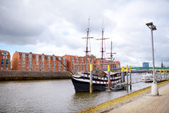 BREMEN, GERMANY - MARCH 23, 2016: A ship in front of historic facades of houses on embankment of Weser river in Bremen, Germany. Royalty Free Stock Image