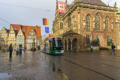 Bremen,Germany, 19 November 2017. Market square in Bremen-flags on the town hall. Tram rides on the square. City street after rain royalty free stock images