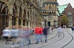 Bremen Tyskland - den suddiga människan figurerar att korsa gata- och spårvagnspåren framme av det historiska stadshuset och domk royaltyfri bild