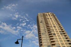 Brend ny hög löneförhöjningbyggnad mot blå himmel Arkivfoto