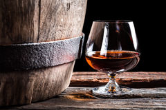 Brendy glass and old oak barrel. Isolated on a black background Stock Photos