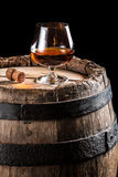 Brendy glass on old wooden barrel Stock Photo