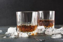 Brendy leggermente caldo in vetri e cubetti di ghiaccio su superficie grigia contro fondo scuro immagini stock libere da diritti