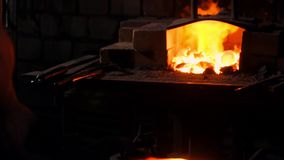 Breng heet metaal van de oven ertoe om een pijluiteinde te maken Hamerslagen op het hete metaal Vonken die van metaal alles bij e stock footage