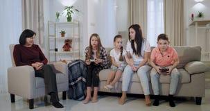 In brengt hij woonkamer een moeder met drie jonge geitjes en oma samen een goede tijd terwijl jonge geitjes binnen spelend aan ee stock footage