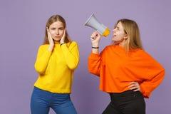 Brengt jong blonde twee zustersmeisjes in kleurrijke kleren samen die oren behandelen met handen, schreeuw op megafoon stock fotografie