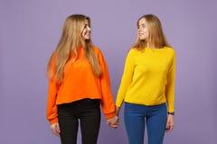Brengt vrij jong blonde twee zustersmeisjes die in kleurrijke kleren samen handen houden bekijkend elkaar op pastelkleur royalty-vrije stock fotografie