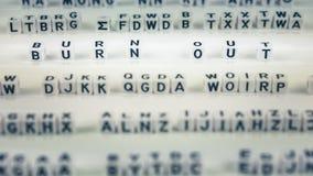 Brennen Sie die Würfelbuchstaben aus, die heraus zwischen anderen unscharfen lettters hervorgehoben werden Stockbilder