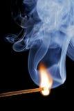 Brennende Abgleichung über einem schwarzen Hintergrund, mit Rauche Stockbild