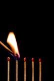 Brennende Abgleichung auf schwarzem Hintergrund Stockbilder