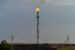 Brennende Fackel an der Raffinerie gegen den grauen Himmel Lizenzfreies Stockbild
