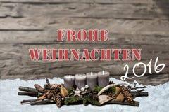 Brennende graue Kerze der Dekoration 2016 der frohen Weihnachten verwischte Hintergrundschnee-Textnachrichtdeutschen Stockfotos