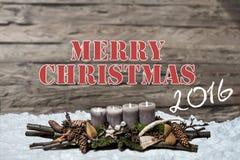 Brennende graue Kerze der Dekoration 2016 der frohen Weihnachten verwischte Hintergrundschnee-Textnachrichtenglisch Stockbild