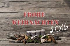 Brennende graue Kerze der Dekoration 2016 der frohen Weihnachten verwischte Hintergrundtextnachrichtdeutschen Stockbild