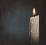 Brennende Kerze über dunklen Hintergründen Stockbild
