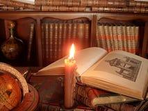 Brennende Kerze, alte Bücher und Kugel. Lizenzfreies Stockbild