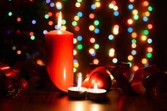 Brennende Kerze auf einer Tabelle mit Weihnachtsdekorationen Stockfoto