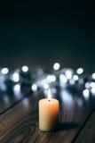Brennende Kerze auf einer Tabelle mit Weihnachtsdekorationen Stockbild