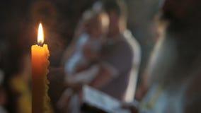 Brennende Kerze auf Hintergrund des Vaters mit dem Kind bereit zum Kirchenritual stock video footage