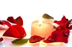 Brennende Kerze in den rosafarbenen Blumenblättern Stockfotos