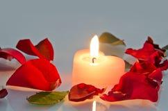 Brennende Kerze in den rosafarbenen Blumenblättern Lizenzfreie Stockfotos