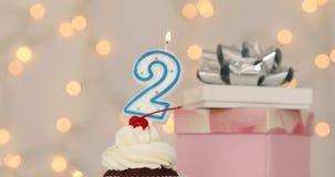 Brennende Kerze der Nr. 2 auf Geburtstagskuchen stock footage