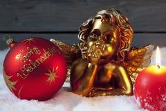 Brennende Kerze der Weihnachtskugel goldenes putto auf Stapel des Schnees Lizenzfreie Stockfotografie