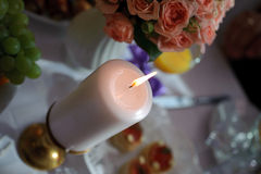 Brennende Kerze, die auf Tabelle steht Stockfotos
