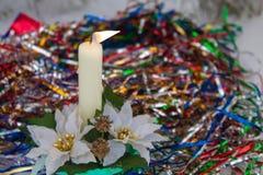 Brennende Kerze Mehrfarbige Dekorationen Wintertaggelb stockfotos